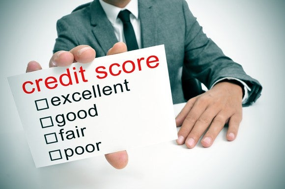 "A man in a suit holds up a card reading ""credit score,"" with checkboxes for ""excellent,"" ""good,"" ""fair,"" and ""poor."""