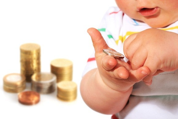 Baby holding coins, with money stacked in the background