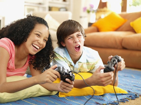 Two kids play a console game while lying on the floor.