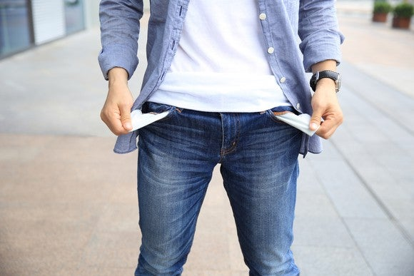 A person turning their pant pockets inside-out to signify they're broke.