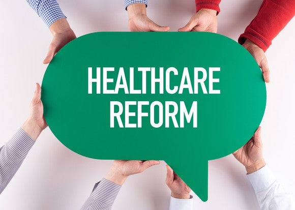"""Hands holding cut-out caption with """"healthcare reform"""" printed on it"""