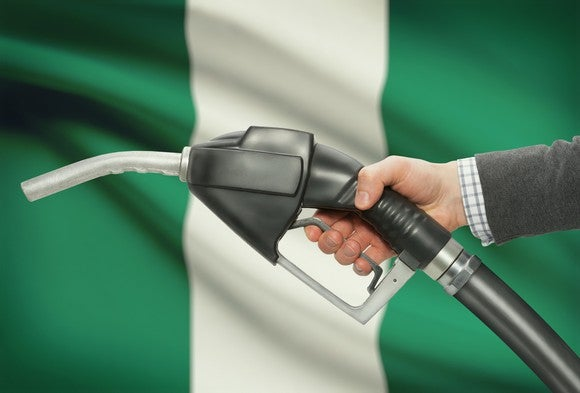 A hand holding a fuel pump nozzle with the Nigerian flag in the background.
