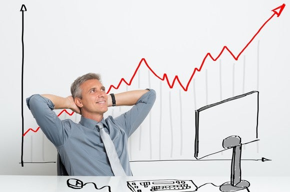 A businessman sitting in front of a rising stock chart.