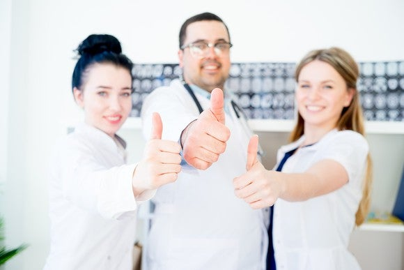 Three doctors making thumbs up gesture.