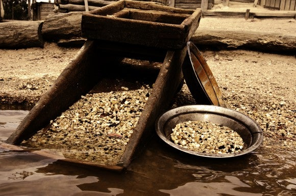 Gold panning tools full of gold, sitting on the edge of a body of water..