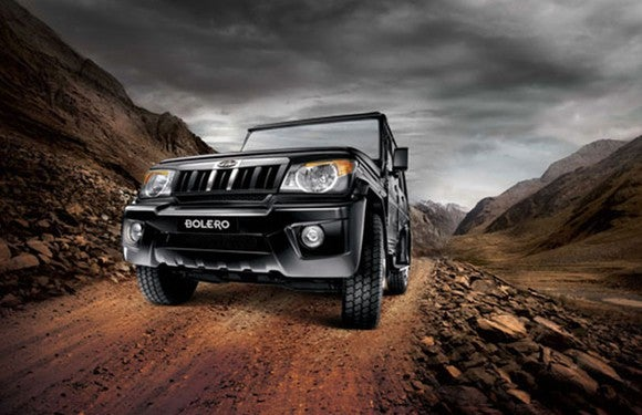 A black Mahindra Bolero, a rugged-looking SUV, on an unpaved mountain road.