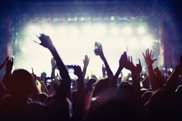 Fans at a concert put their hands in the air.