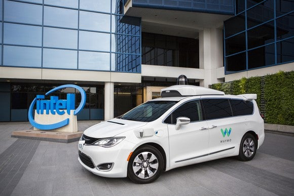 A white Chrysler Pacifica Hybrid minivan with Waymo logos and visible self-driving sensor hardware is parked in front of an Intel building.
