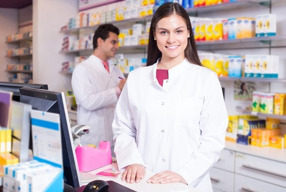 A pharmacist stands behind a drugstore counter.
