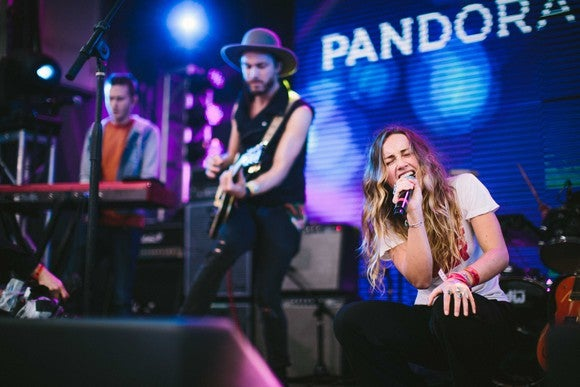 "A Pandora concert as a band performs with ""Pandora"" on a screen behind them."
