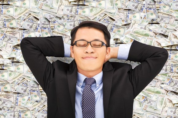 Sleeping business man on top of pile of money