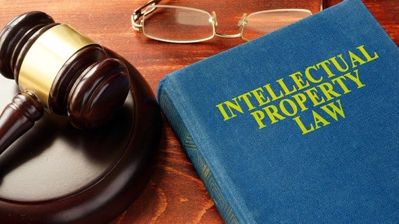 Intellectual property law book with a gavel on a table.