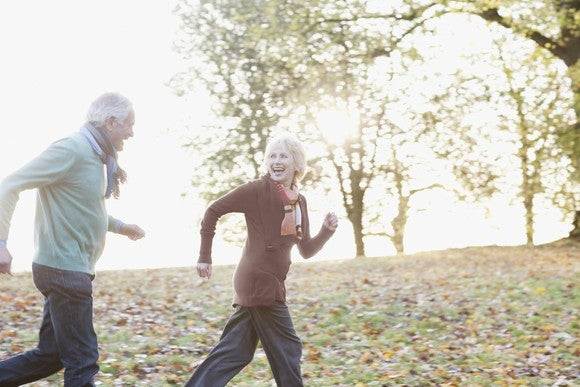 Older man and woman running through park