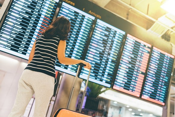 A woman looking at a departure and arrival board in an airport.