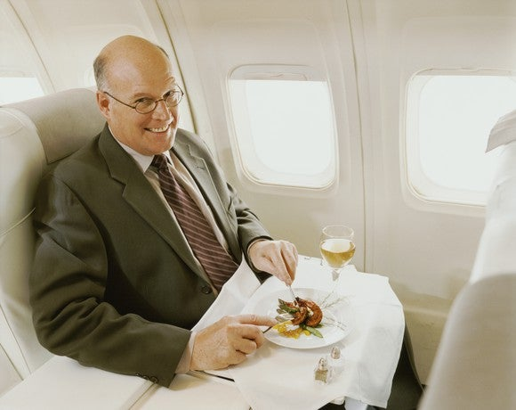 A man in a suit eating a meal aboard a plane in first class.