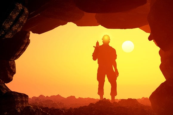 A man standing in the mouth of a mine with the setting sun in the distance.