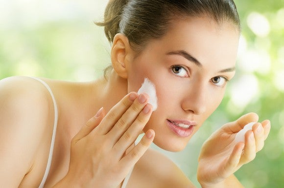 A woman applies face cream.