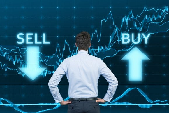 A man looking at a stock screen with buy and sell symbols.