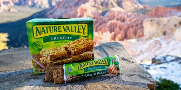 A box of Nature Valley granola bars with mountains in the background.
