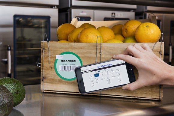 An IBM blockchain solution on a mobile phone being used to track a crate of oranges.