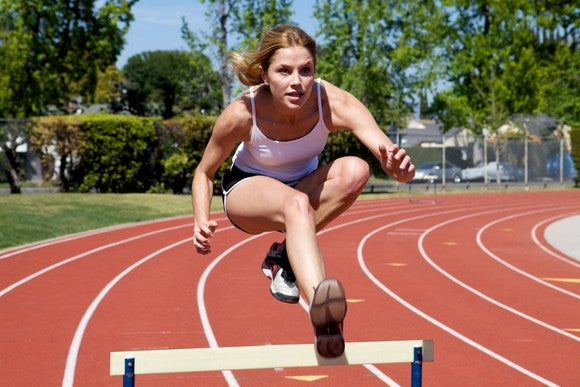 Female athlete leaping over hurdle on circular track.