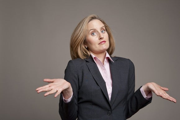 A businesswoman shrugs with a confused look on her face.