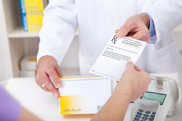 A pharmacist is handing a customer a perscription.