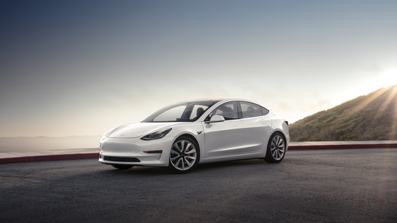A white Tesla Model 3 with the sun shining over a mountain in the background.
