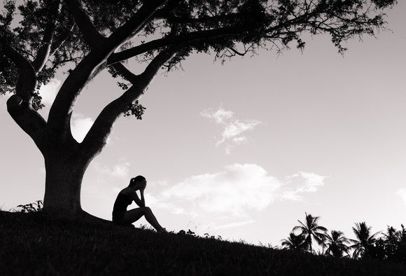 The silhouette of a woman with her hands in her face, on a hill, by a tree.