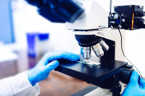 A biotech lab researcher examining a sample with a microscope.