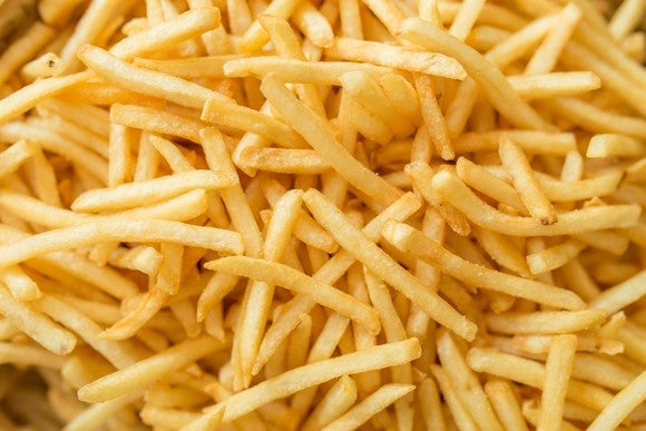 A close-up shot of a plate full of French fries.