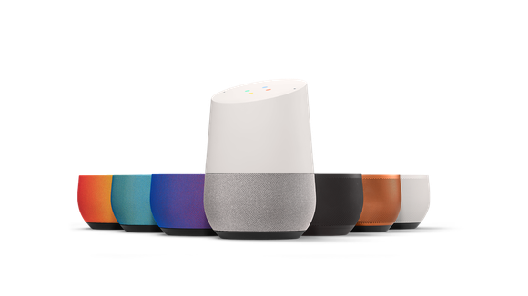 A Google Home alongside different colored, interchangeable bases.