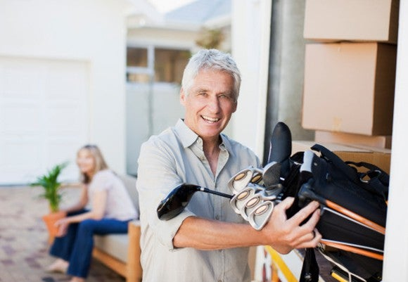 Smiling retiree grabbing his golf clubs.