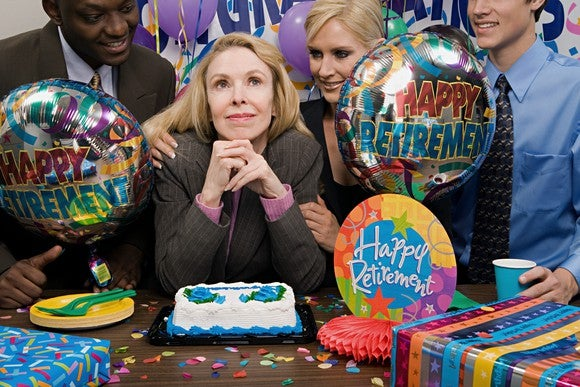Middle-aged woman at her retirement party, with a cake in front of her and balloons, presents, and coworkers.