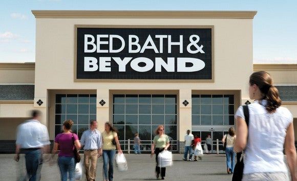 A view of a Bed Bath & Beyond from the parking lot, with people entering and exiting the front doors.