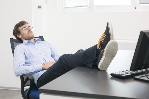 A man naps with his legs up on his desk.