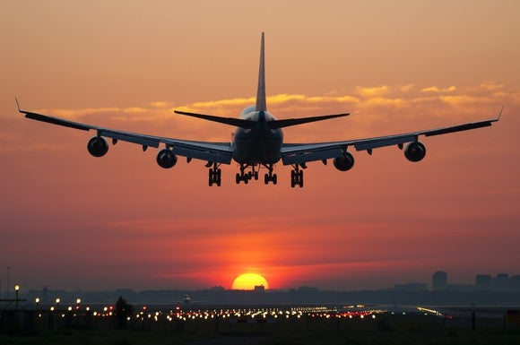 An airplane landing at sunset.