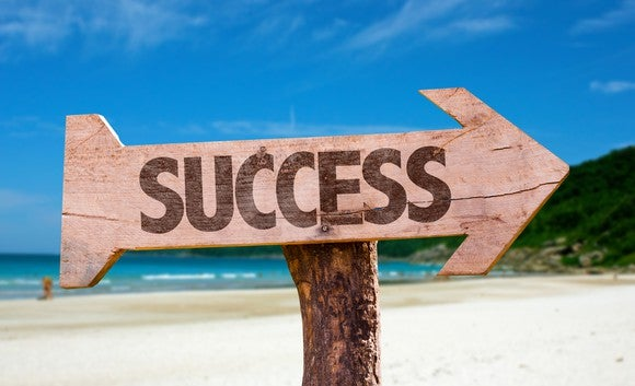 "arrow-shaped sign by a beach, with ""success"" written on it"