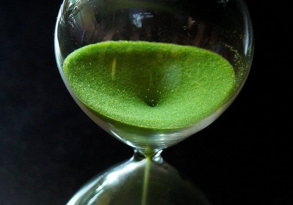 close up of hourglass with green sand falling through it