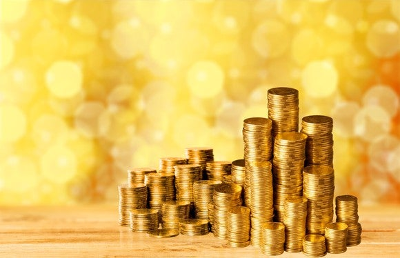 Many stacks of gold coins, some of which are very tall, in front of a glimmering gold background.