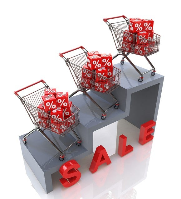 """Shopping carts on steps filled with red blocks showing percent signs with word """"SALE"""" in front of steps"""
