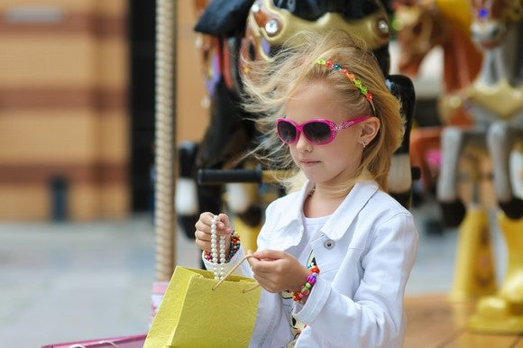 A young girl wearing pink sunglasses, bracelets, and a headband looks at jewelry she has in a yellow shopping bag