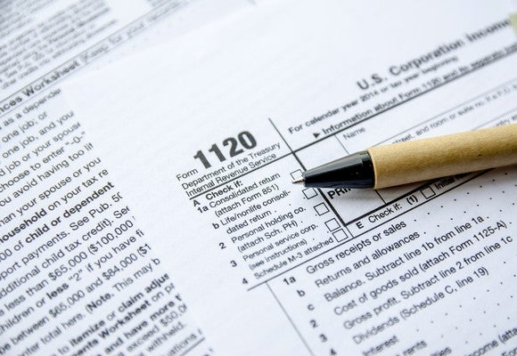 Tax Form 1120 for corporate income tax with a pen lying on top.