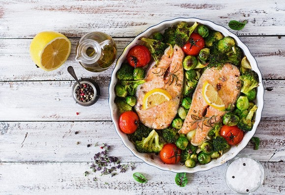 Bowl of colorful salad with salmon steaks on top, next to half a lemon, a bottle of oil, a small bowl of salt, and a container of peppercorns on a whitewashed table