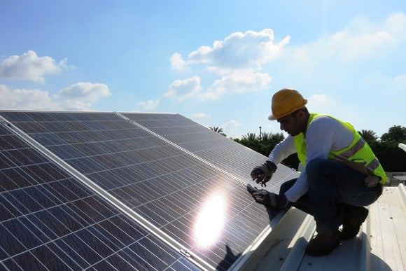 Worker installs a solar panel on an aluminum roof on a sunny day.