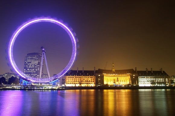 The London Eye ferris wheel lit up at night with part of the London skyline.