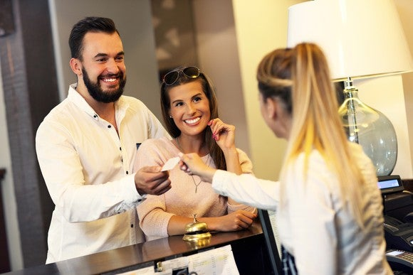 A woman behind a hotel desk hands a room key to a smiling couple.