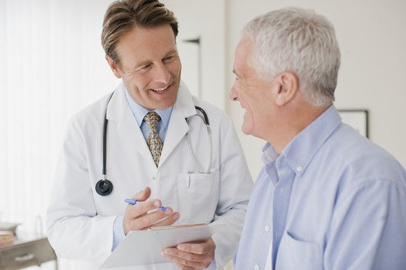 A doctor and elderly man having a jovial discussion.