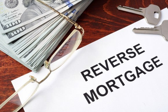 Reverse mortgage paperwork on a table with keys and a stack of money.