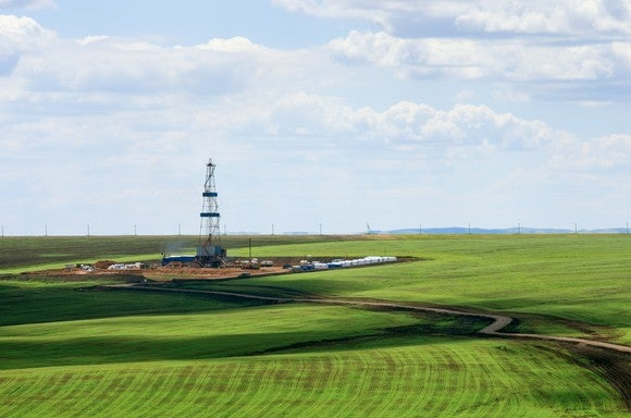 A drilling rig in a green field.
